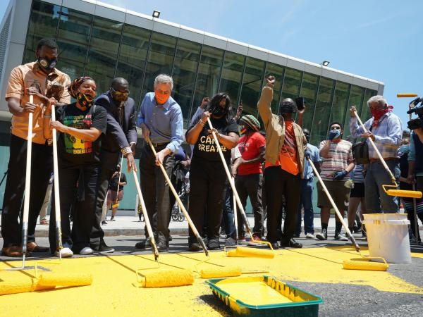 New York City Mayor Bill de Blasio (fifth from left) helps volunteers paint a Black Lives Matter mural in the borough of Staten Island on Friday, as the city marks Juneteenth.