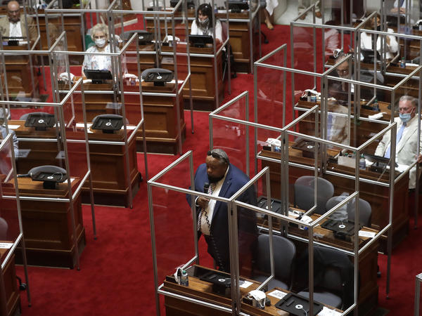 Rhode Island's House Chamber met while separated by plastic protective barriers at the start of a legislative session earlier this month in Providence, R.I.