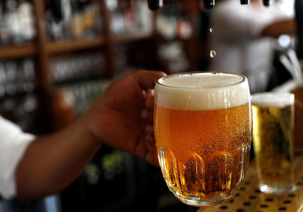 A pint of beer is poured into a glass in a bar in London, Britain June 27, 2018.