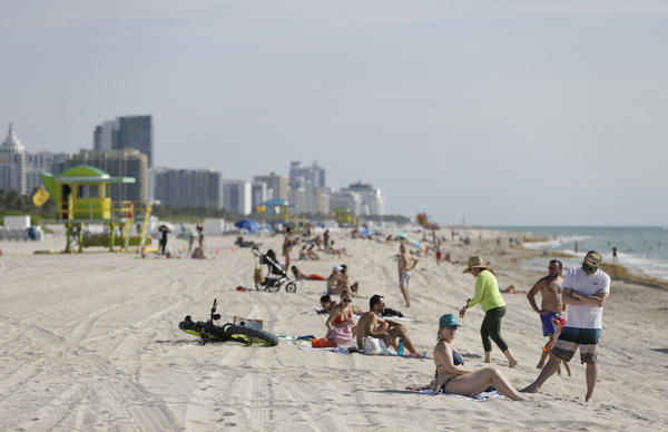 Beach goers enjoy a day on the sand and in the water, Wednesday, June 10, 2020, on Miami Beach, Florida's famed South Beach. Beaches in Miami-Dade County opened with restrictions Wednesday after having been closed for 12 weeks due to the COVID-19 outbreak. (AP Photo/Wilfredo Lee)