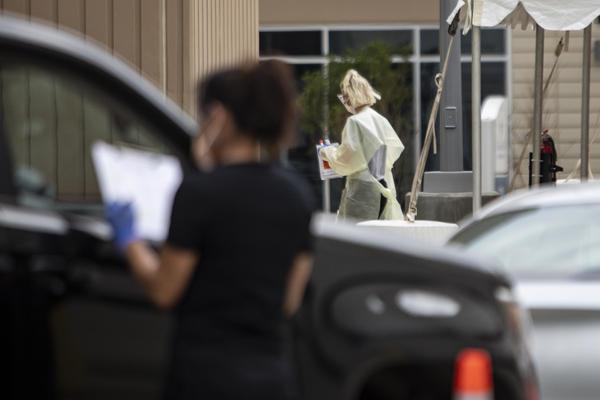 Un grupo de personas se somete a pruebas de COVID-19 en un sitio de drive thru en el sur de Austin.