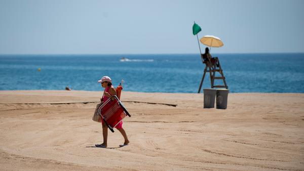 A woman passes a lifeguard this week on the beach in Lloret de Mar, Spain. The European Union is considering which countries should be allowed to send tourists to its member nations as travel restrictions begin to ease in the pandemic.