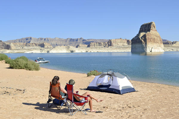 Campers sit on Lone Rock Beach at Lake Powell.