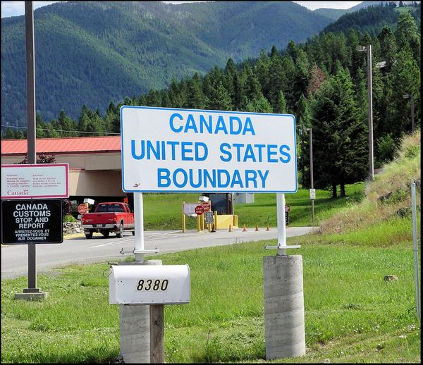 Vehicles drive past a sign at the Montana-Canada border.