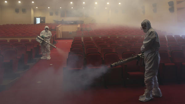 Workers wearing protective suits fumigate an art hall with antiseptic solution as a precaution against the spread of the Middle East respiratory syndrome in Seoul, South Korea, in June 2015.