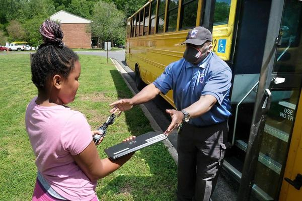 A Charlotte-Mecklenburg Schools employee delivers devices to help students learn from home.