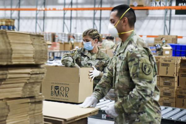 Members of the California Army National Guard assemble emergency food kits at the Los Angeles Regional Food Bank.