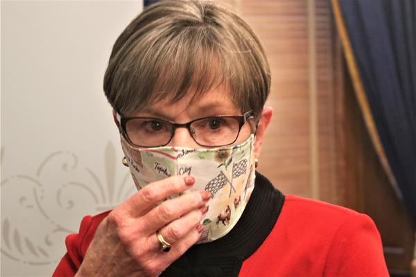 Kansas Gov. Laura Kelly puts on a mask after a news conference on June 22.
