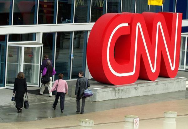 Pedestrians enter CNN Center, the headquarters for CNN, in downtown Atlanta, Wednesday, Jan. 17, 2001.