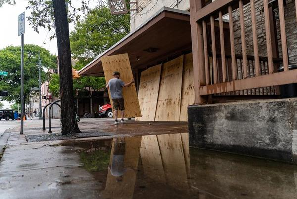 An employee boards up a bar on Sixth Street in Austin after Gov. Greg Abbott closed bars in Texas for the second time in three months because of the COVID-19 pandemic.