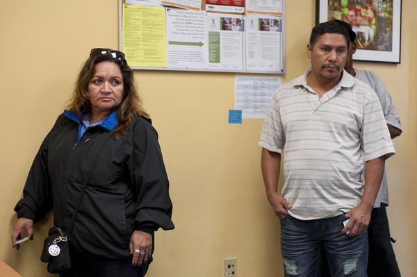 Judith Prado, left, and Marcos Perez, wait in line at the Manna Food Center in Gaithersburg, Md.