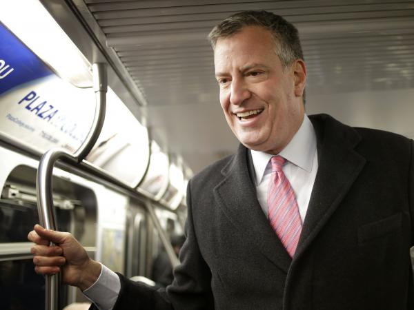 New York City mayoral candidate Bill de Blasio rides the subway while greeting commuters in New York on Monday.