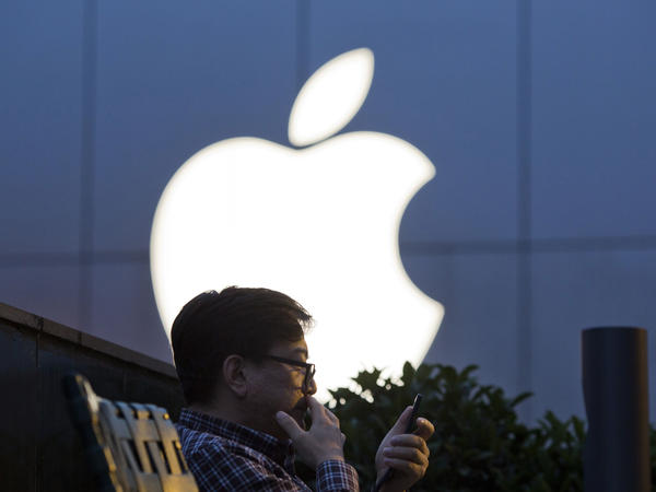 A man uses his mobile phone near an Apple store logo in Beijing. The latest iPhone is expected to include facial recognition as an unlocking feature but do away with the home button.