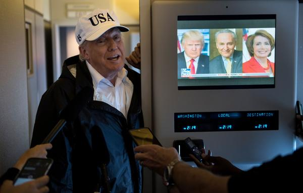 President Trump speaks to the press onboard Air Force One while flying back to Andrews Air Force Base from Florida on Thursday.