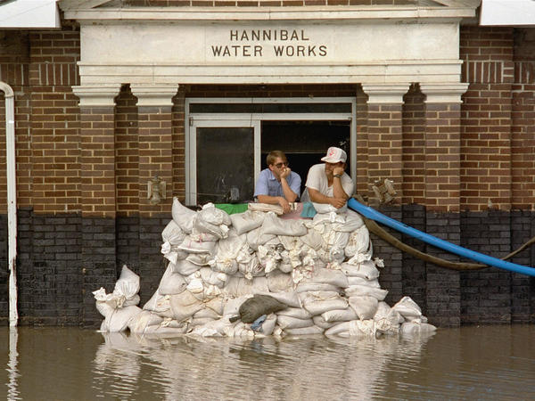 Mike Stone, left, and Andy Sherman in the pumping station for Hannibal, Mo., during a flood in 1993. The city is protected by a flood wall, and flood managers have built up levees to protect against flooding. But scientists warn those structures are making flooding worse.