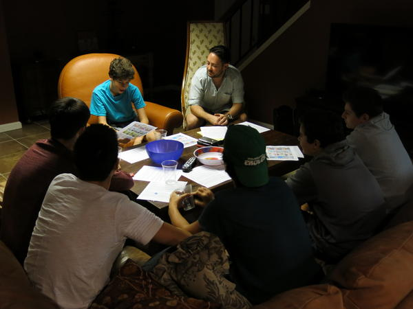 Cody Greenes (center), group leader with Moving Traditions, leads six high school boys in a discussion about sexual assault and consent. The program was designed to discuss difficult topics in an all-male setting.
