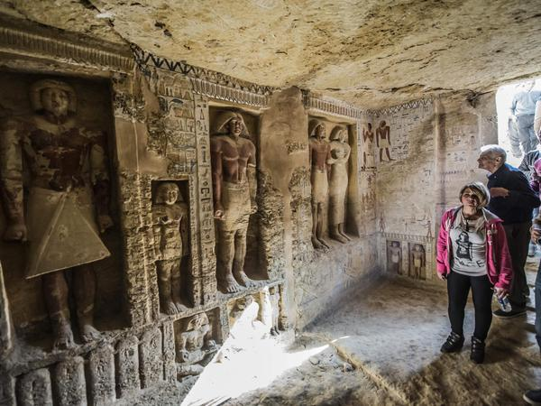 Visitors enter a newly-discovered Egyptian tomb at the Saqqara necropolis on Saturday.