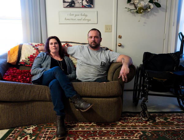 Ret. Sgt. Chris Kurtz and his wife Heather Kurtz pose for a portrait on the couch in their living room.