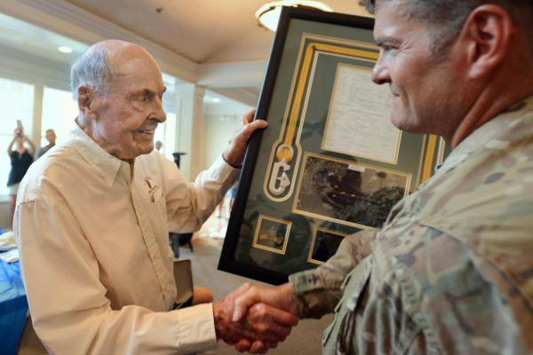98-year-old Normandy survivor Ray Lambert (left) accepts a plaque at a June 2018 ceremony. Fort Bragg paratroopers splashed down in his Moore County neighborhood as part of a salute to his service.