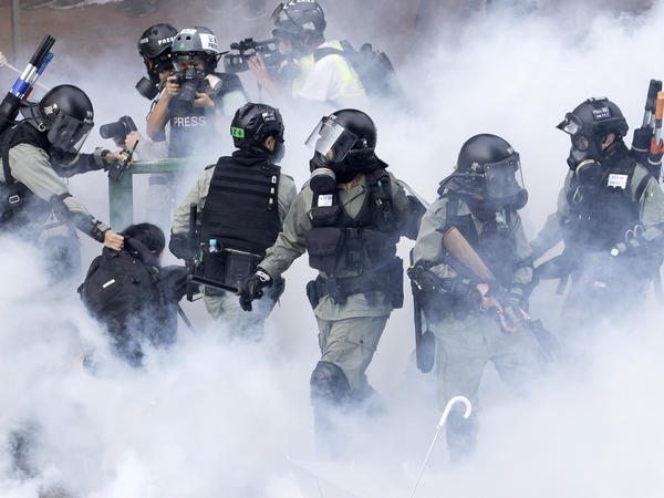 Police in riot gear move through a cloud of smoke as they detain a protester, in November. Freedom House cited the willingness of people in Hong Kong to protest as encouraging.