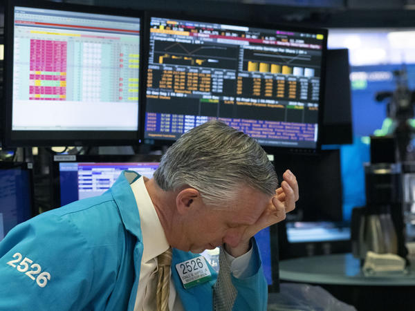 A trader reacts after automatic circuit breakers kicked in and trading was halted temporarily Wednesday at the New York Stock Exchange.