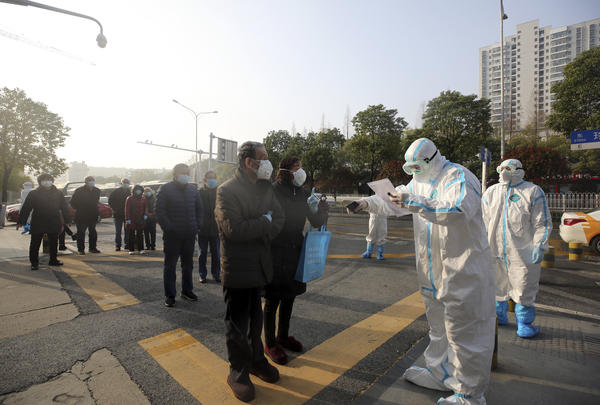 People in Wuhan, China, line up at a facility that tests discharged COVID-19 patients as well as individuals who had been held in isolation.