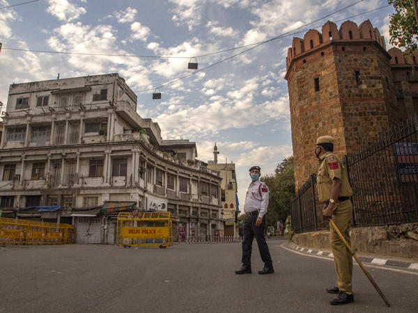 Indian policemen stand guard on a deserted road in New Delhi as India remains under lockdown over the coronavirus.
