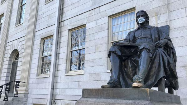 A statue of John Harvard, namesake of Harvard University, wears a face mask last month on the school's campus in Cambridge, Mass.