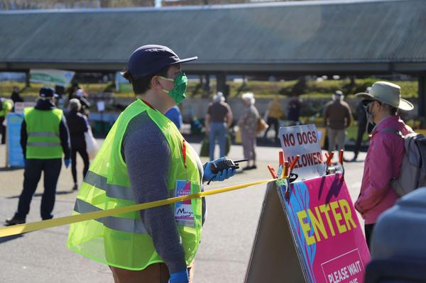 Morgan Henry Kerr of Bellingham's Farmers Market monitors the new market entrance to monitor the number of people in the market so that physical distancing is maintained at all times.