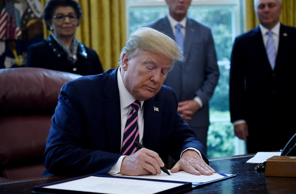 President Trump a new coronavirus economic aid package, largely targeted to support small businesses, in the Oval Office on Friday.