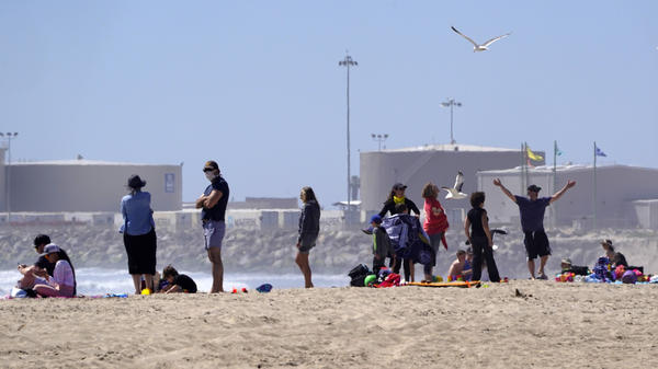 Beachgoers return to Port Hueneme Beach, Calif., on Thursday. Ventura County beaches and parks have been scheduled to reopen this week with some restrictions.