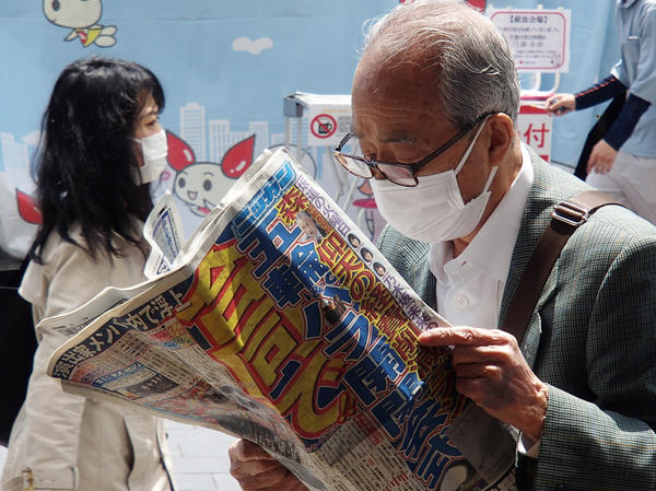 A man reads a sports newspaper on the street amid the COVID-19 pandemic in Tokyo on Tuesday. The move for dentists to administer tests is aimed at relieving the burden on doctors and boosting capacity.