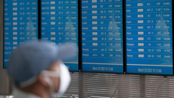 A traveler wearing a face mask looks at the flight board at Reagan National Airport last month in Washington. JetBlue is the first major U.S. airline to require passengers to wear face coverings.