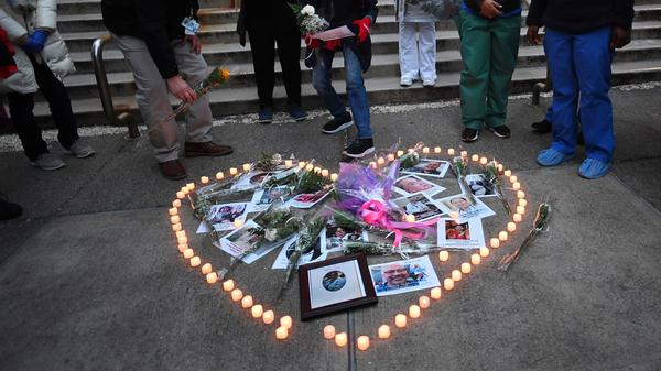 Health care workers light candles outside Mount Sinai Hospital in New York City on April 10 as they mourn and remember their colleagues who have died during the COVID-19 pandemic.