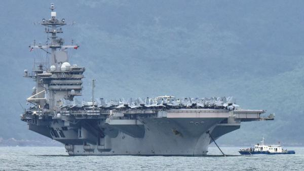 """The acting secretary of the Navy is seeking a more thorough review of """"decisions of the chain of command surrounding the COVID-19 outbreak aboard the USS Theodore Roosevelt."""" The aircraft carrier is seen here as it enters the port in Da Nang, Vietnam, last month."""