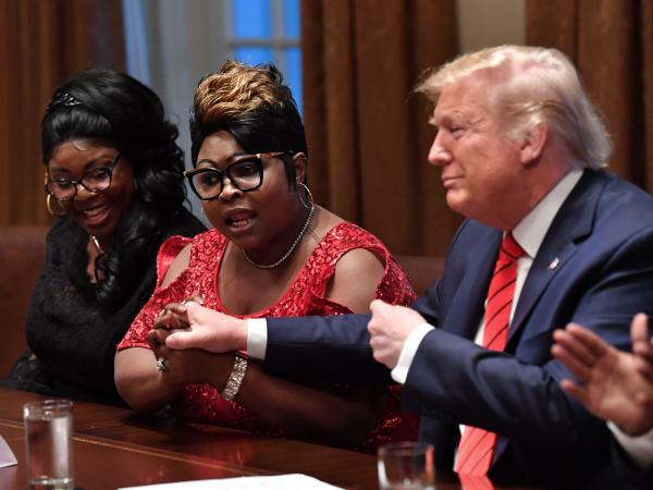 President Trump and Rochelle Richardson — better known as Silk in the social media duo Diamond and Silk — hold hands at a February event. Richardson is on the advisory board of Black Voices for Trump.
