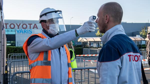 A worker wearing protective gear checks an automobile assembly line worker's temperature at the entrance to a Toyota plant in Onnaing, France, on April 21. U.S. auto plants are preparing to reopen with new coronavirus safety protocols.