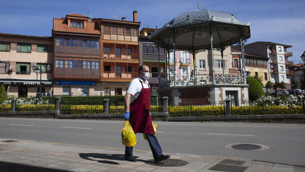 The new EU economic forecast reflects a total drop of 9 percentage points since last fall's forecast, as businesses have been shut down or forced to operate at severely limited capacity. Here, a man delivers a butcher shop order in Norena, Spain, on Wednesday.