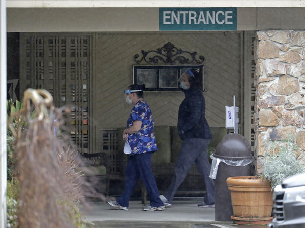 Two workers approach the entrance to Life Care Center in Kirkland, Wash., on March 13. An association that represents nursing homes is asking for billions of dollars in federal relief funds to cope with the coronavirus crisis.