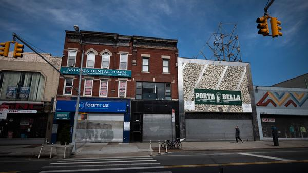 A woman wearing a mask walks past closed store fronts in the Astoria neighborhood of Queens on April 15 in New York City. States are beginning to implement phased reopening plans, in part to help businesses hit hard by the coronavirus.