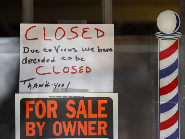 """""""For Sale By Owner"""" and """"Closed Due to Virus"""" signs are displayed in the window of Images On Mack in Grosse Pointe Woods, Mich. Congress is considering ways to help those struggling during the economic downturn and stabilize businesses hoping to reopen."""