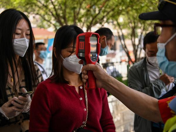A worker checks a passenger's body temperature on Tuesday after arriving in Wuhan, China. Earlier this week, authorities found at least six new cases of the coronavirus.