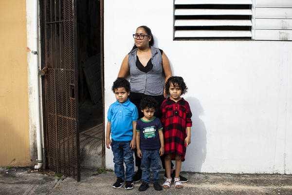 Elia Gonzalez, 25, stands with her children Jesiel, 5, Ansiel, 4 and Angellia, 6, at the entrance to their home in Río Piedras, San Juan, Puerto Rico. Since her partner lost his work, food stamps have not been enough to keep Gonzalez's family fed during the pandemic.