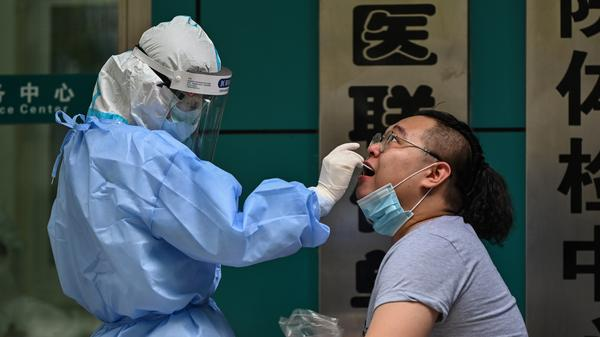 A man gets tested for the coronavirus Wednesday in Wuhan, China, the cradle of the global pandemic. Authorities plan to test the city's entire population after new cases emerged for the first time in weeks, according to state media.