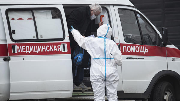 A medical worker helps a man suspected of being infected with the coronavirus out of an ambulance at a hospital in Kommunarka, outside Moscow.