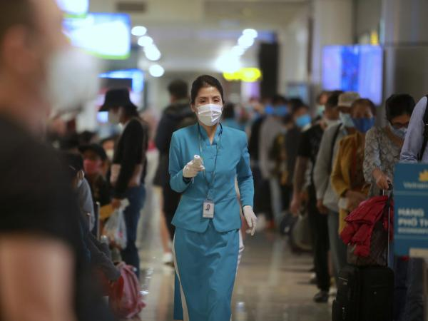 An airline employee holds a thermometer to check boarding passengers at Noi Bai International Airport in Hanoi, Vietnam. After three weeks with no local cases reported, Vietnam has reopened schools, businesses, factories and tourist attractions.