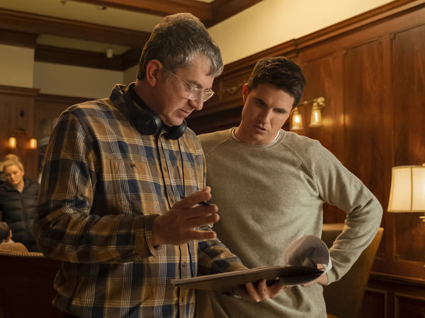 Greg Daniels talks over a script with actor Robbie Amell on the set of Upload.