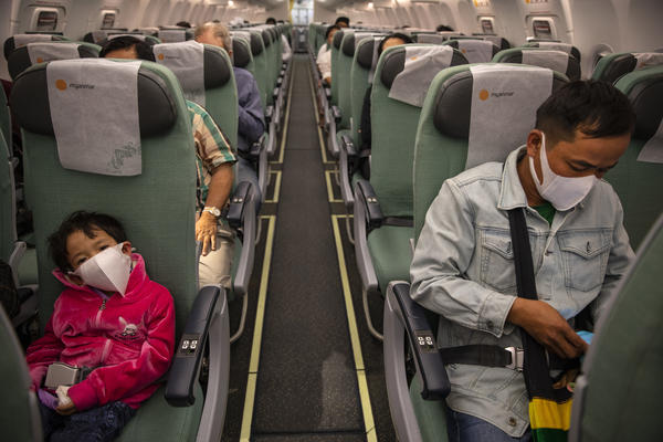 Passengers wear masks on a Myanmar National airlines flight out of Yangon. Many airlines now require passengers to don masks.