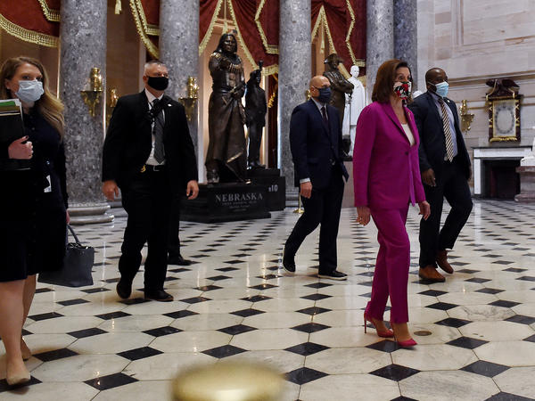 House Speaker Nancy Pelosi, D-Calif., walks past the Statuary Hall ahead of floor debate on a record $3 trillion coronavirus response package Friday to fund the fight against the pandemic and provide emergency payments to millions of Americans.