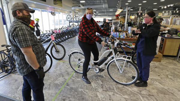 Store manager Josh Hayden, left to right, talks with Kay Amey and Jackie Gee about a new bicycle at Eddy's Bike Shop on Tuesday in Willoughby Hills, Ohio. Bike shops in most states were exempt from shutdown orders and sales have been up.